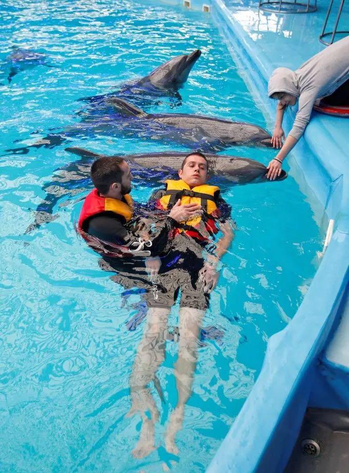 2016年3月1日,乌克兰基辅,在东部与亲俄武装作战中受伤的乌克兰士兵接受海豚治疗。海豚治疗起源于上世纪70年代早期,在治疗过程中,病人会和海豚游泳,抚摸海豚并给它们喂食。这个治疗的目的是增强病人的感知能力。